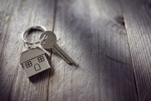 House key on a house shaped keychain resting on wooden floorboar